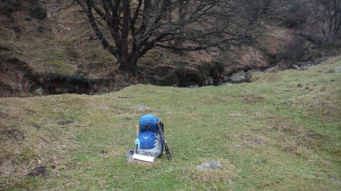 Blue osprey rucksack on a flat grassy river bank