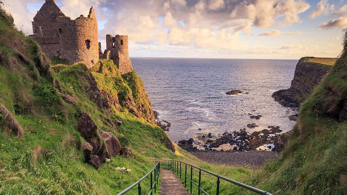 steps and rails down to ruins Dunluce castle by the sea Mountain Ways Ireland - Walking Holidays in Ireland,The Antrim Glens and Causeway Coast Walking Holiday
