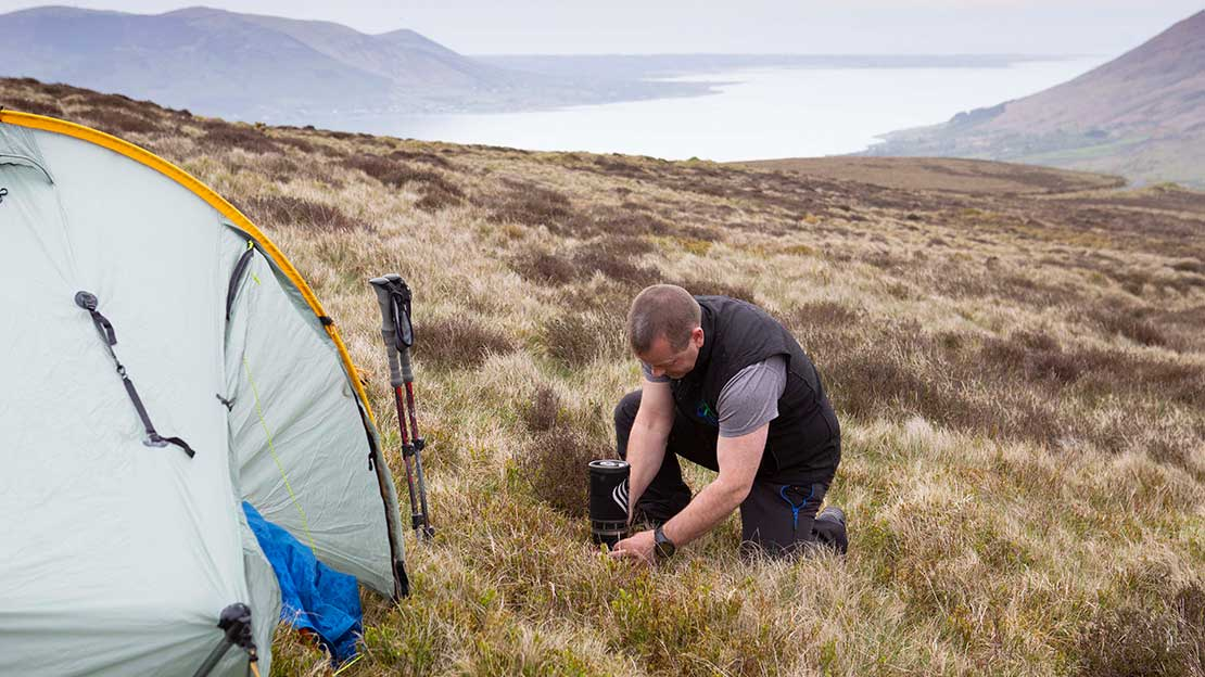 Mountain Ways Ireland guide lighting a jetboil on mountainside alongside tent