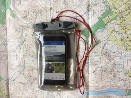 Iphone with Mountain ways ireland website open in a clear waterproof aquapac case sitting on Mournes Map
