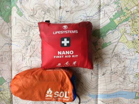 Lifesystems nano first aid kit and sol emergency bivvy bag sitting on a mourne mountain map