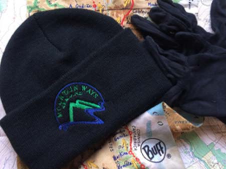Mountain Ways Ireland logoed black beanie , gloves and buff on top on a map -Blog- What's in my rucksack?