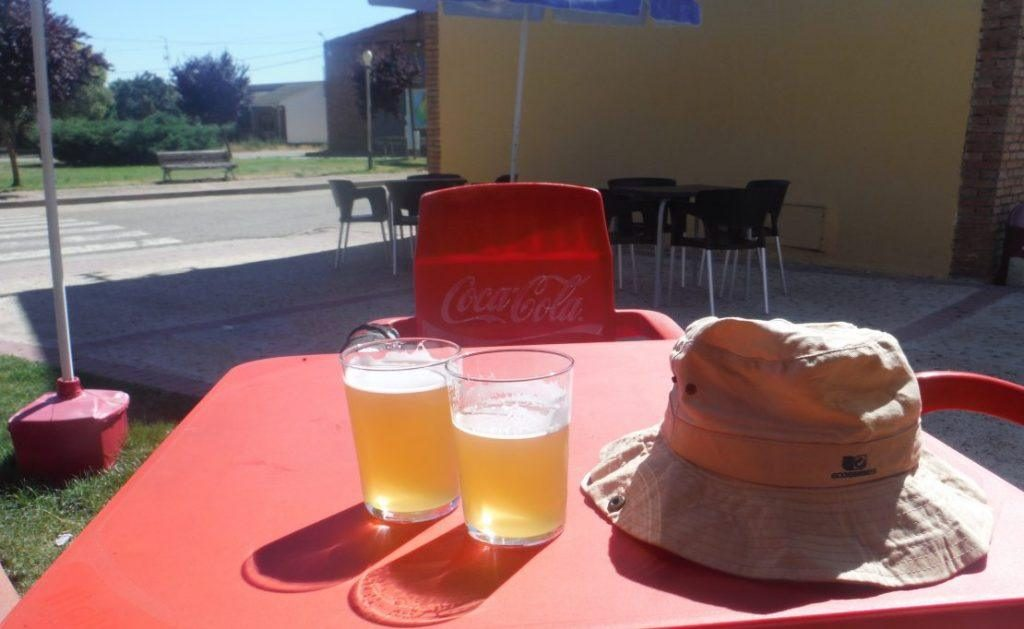 table with two beers and sunhat on the camino.