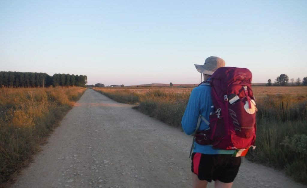 woman wearing a well balanced rucksack with the long road of the Camino de Santiago stretching in front.