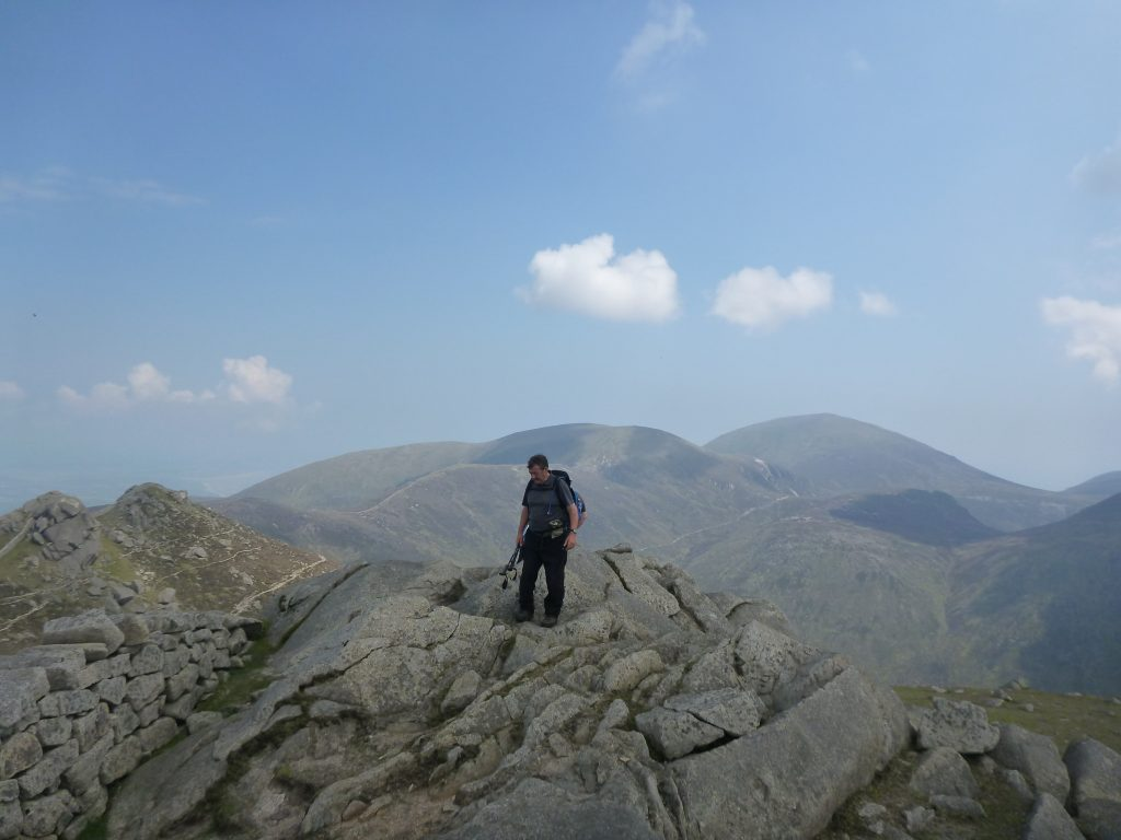 lone Hiker standing on rocky peak in the Mourne Mountains