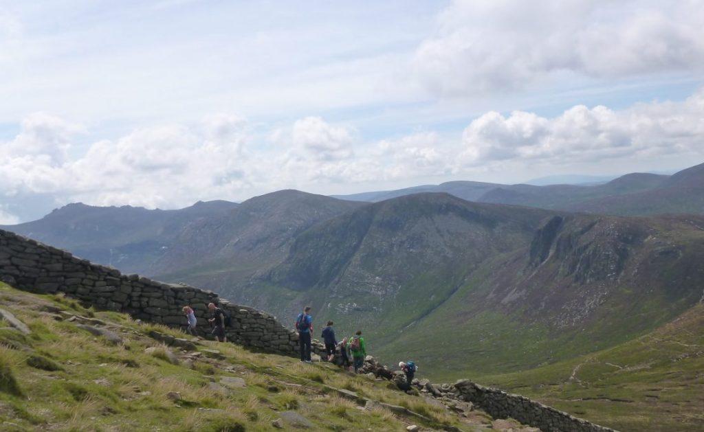 Group climbing Mountain along wall