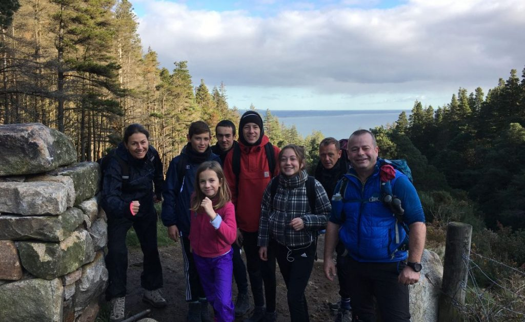 Group of hikers at wall between forest and Mountain Slieve Donard