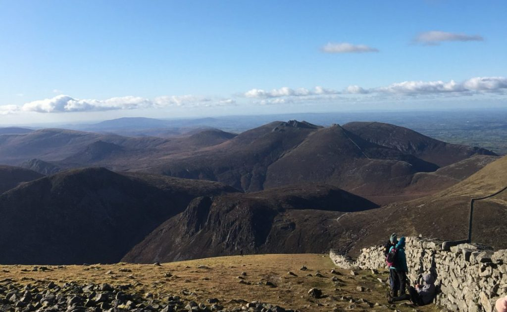 Hikers along wall summit view blue skies Slieve Donard