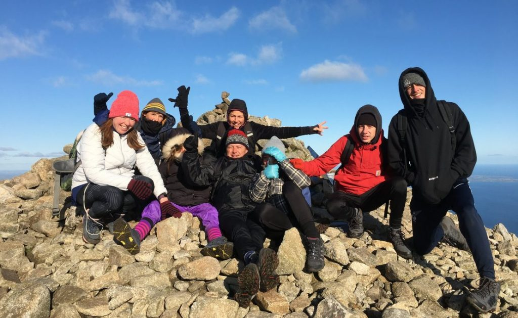 Group of hikers celebrate on summit cairn Slieve Donard
