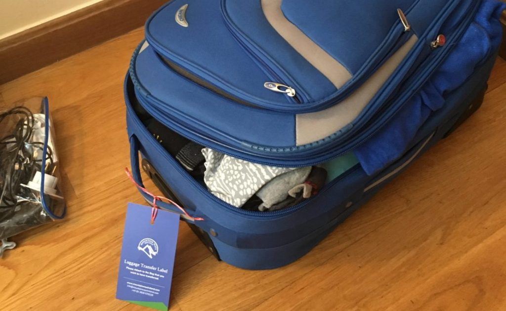 Blue suitcase on floor with Mountain Ways Ireland Transfer Luggage Label