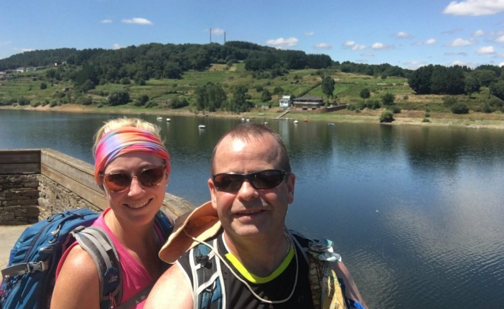 A man and woman with sunglasses selfie against river backdrop on the Camino